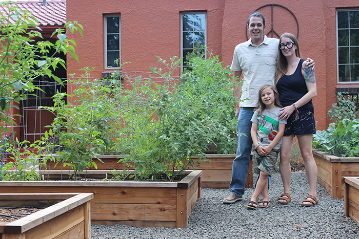 Tracy, Ben and their son stand in their veggie garden