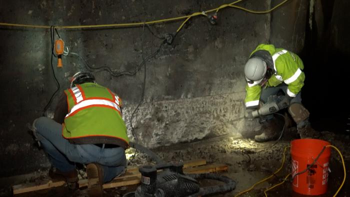 Workers repair section of damaged concrete inside Dillon Dam outlet tunnel