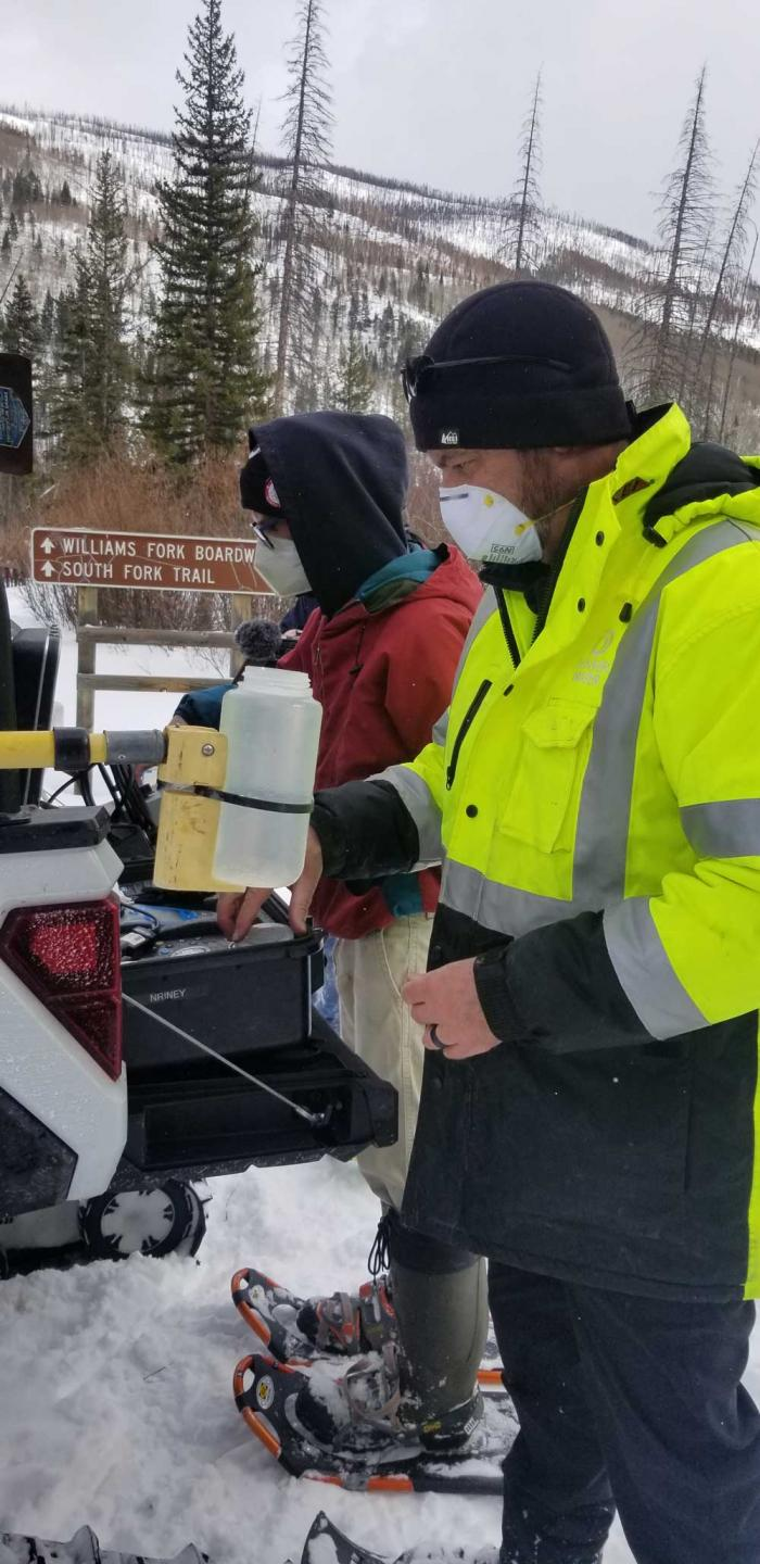 Two men stand next to a pickup full of testing equipment. It's cold and snowy. They're wearing masks and heavy coats.