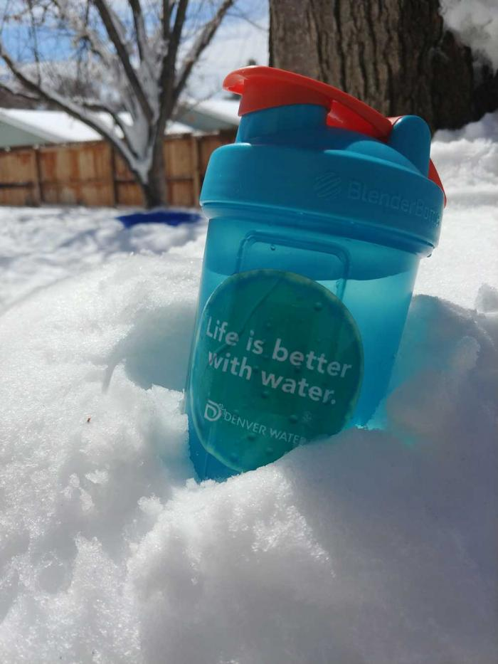 """A water bottle, with a sticker that says """"Life is Better With Water"""" and a Denver Water logo, rests in a pile of snow."""