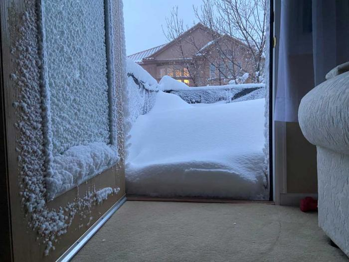 A snow-encrusted door opens onto a snow-covered patio, with another house seen in the distance.