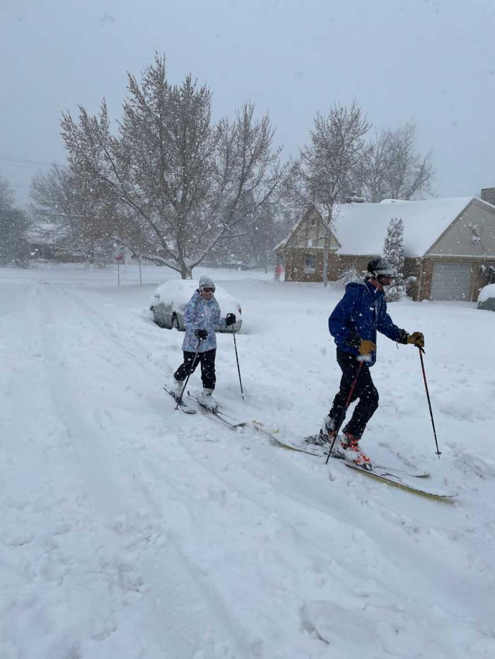 Two people cross-country ski down a street amid the snow.