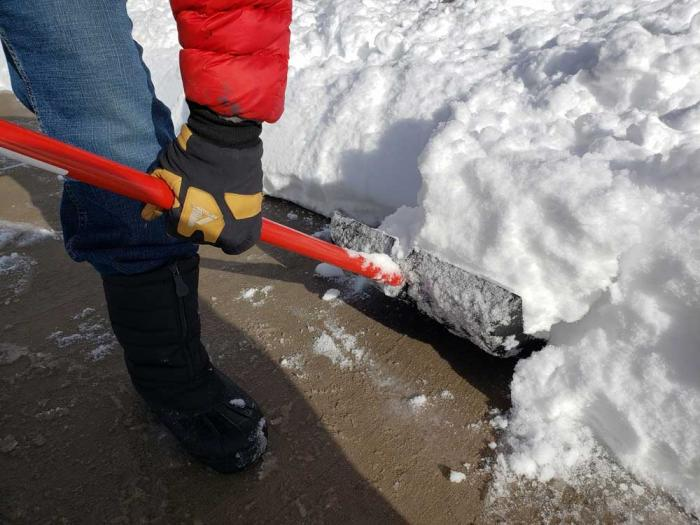 A shovel full of snow is lifted off the sidewalk.