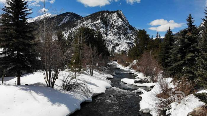 A dark creek flows through snow-covered mountains with trees under sunny, blue skies.