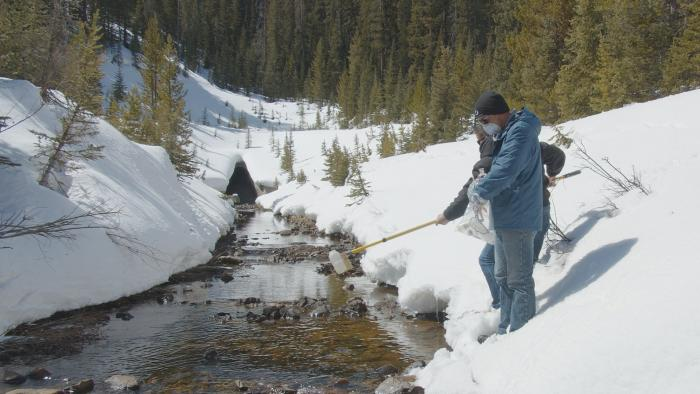 Two men stand in the snow next to a mountain creek. One holds a pole, attached to a bottle that will scoop up a water sample.