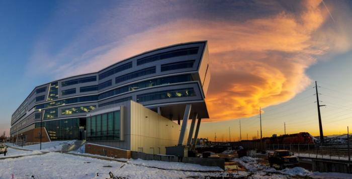 Denver Water's new Administration Building, all the angles lit up against the billowing, orange-colored cloud at sunset.