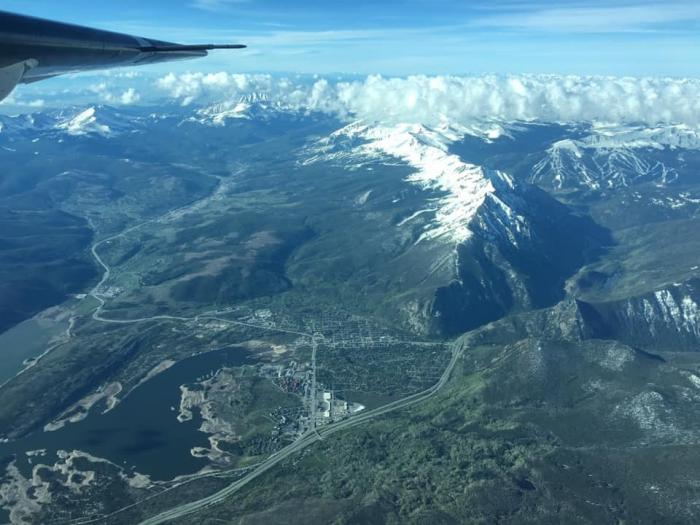 A mountain range seen from the air, with a piece of a plane's wing in the upper edge of the picture.