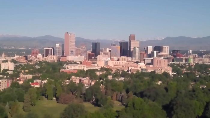 Downtown Denver is seen against blue skies and the mountains.