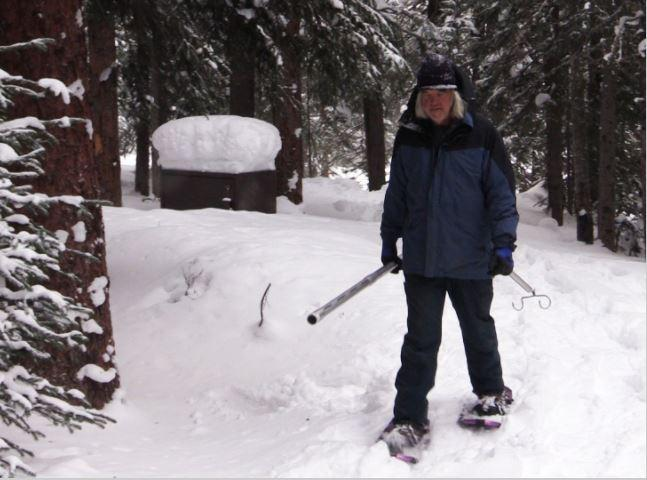 A man holding a metal tube snowshoes through the forest.