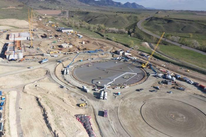 A bird-eye view of the site of the Northwater Treatment Plant, with workers in the foreground and Ralston Reservoir seen in the distance.