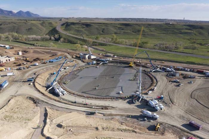 A view of the round base of the storage tank with Highway 93 rising into the green hills at the top of the picture.