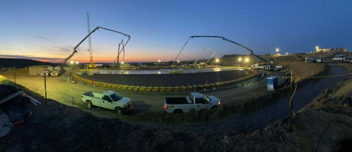 A work site lit by construction lights, with trucks and concrete pumps, and the dawn in the distance.