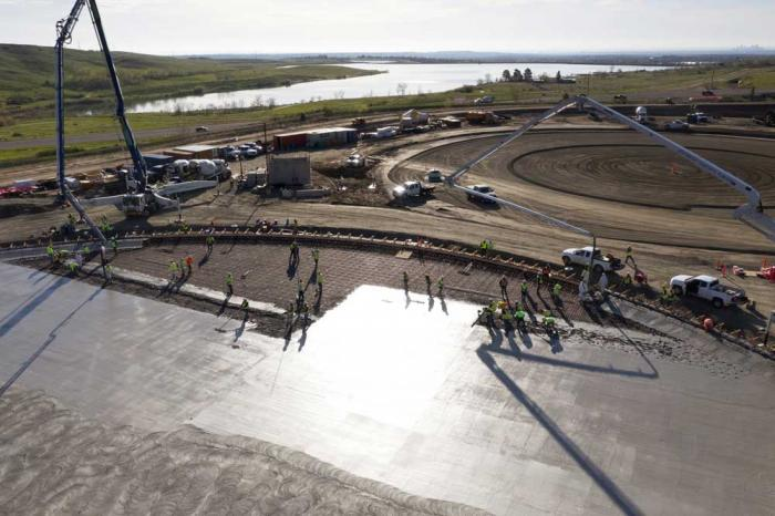 A view from a done flying over the round base of the storage tank, while concrete is poured on it.