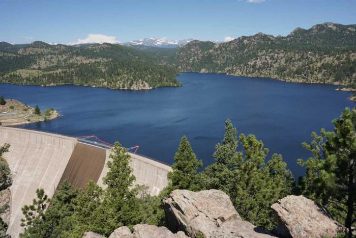 A large dam holds back a huge lake of blue water under a blue sky.