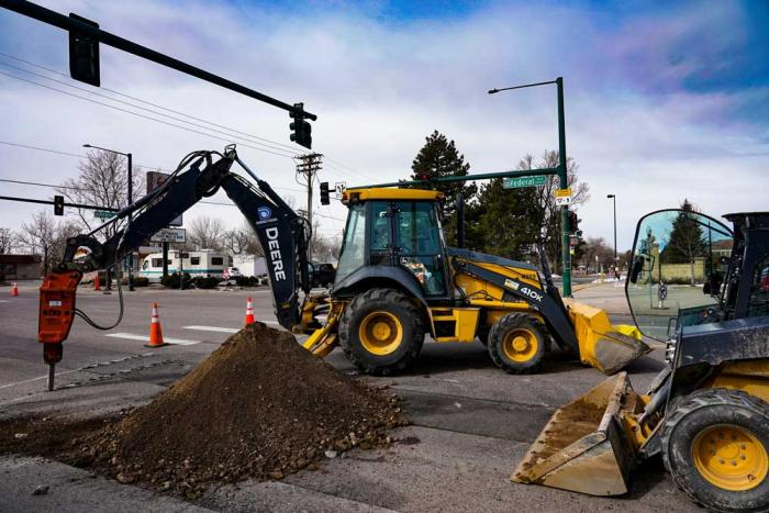 An excavator fills a hole with dirt under a street sign for Federal Boulevard.