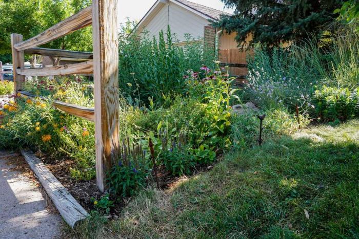 A full garden next to a split-rail fence along a sidewalk in a neighborhood.