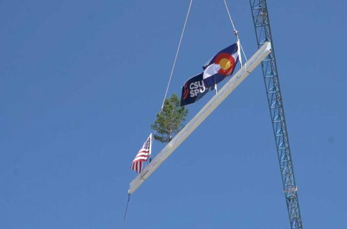 A white steel beam with flags fluttering in the air dangles on cables below a crane.