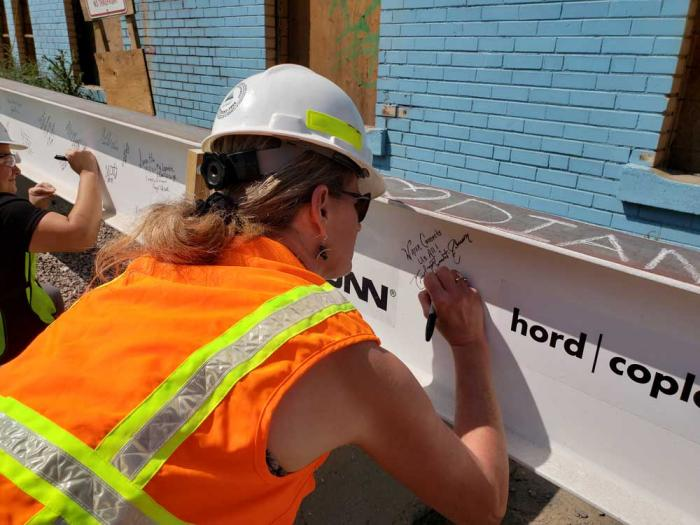 A woman in a hardhat signs her name on a steel beam.