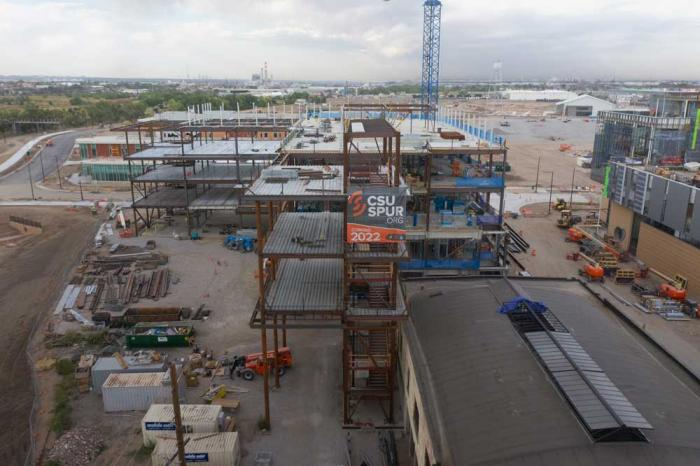 A building under construction with a banner for CSU Spur.