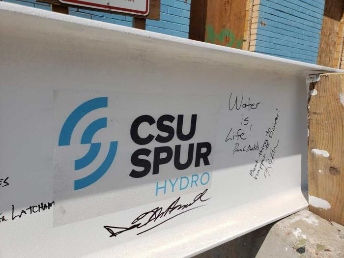 A steel beam, painted white, with the logo of the CSU Spur Hydro building and signatures.