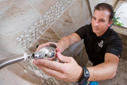 Denver water worker replacing showerhead