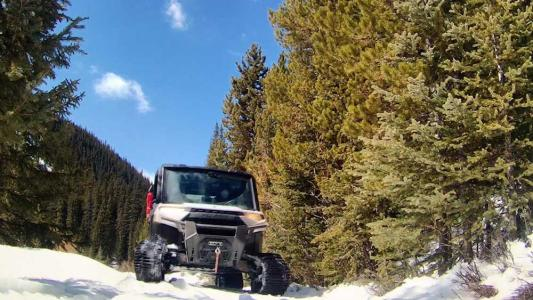 An all-terrain vehicle comes toward the camera, over a snow-covered road surrounded by trees.