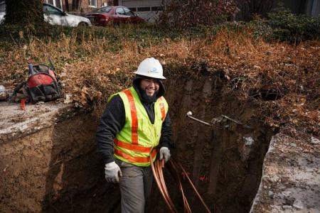 A worker stands in a hole dug in the ground, smiling, holding a coil of copper pipe.