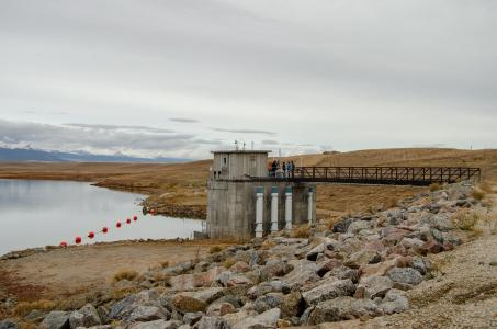 People stand on a bridge looking at equipment that is part of the Antero Reservoir dam.