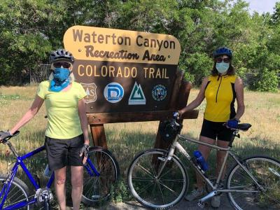 Two of the first recreationists pose by Waterton Canyon sign on reopening day, Monday, June 15, 2020.