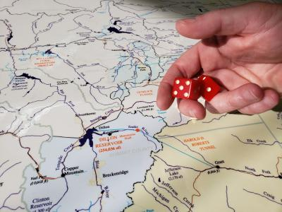 A map of Denver Water's collection systems with a hand holding a pair of dice.