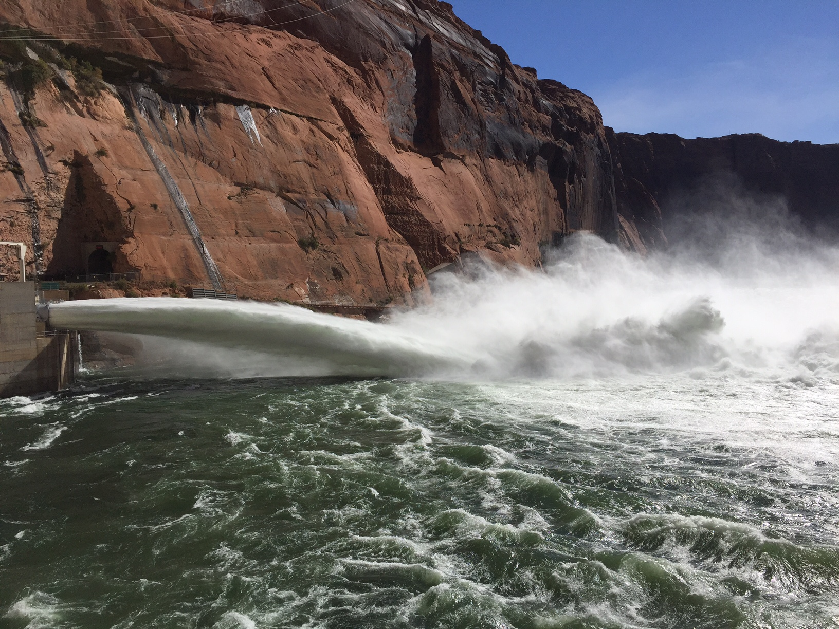 Water sprays from Glen Canyon Dam into the Colorado River