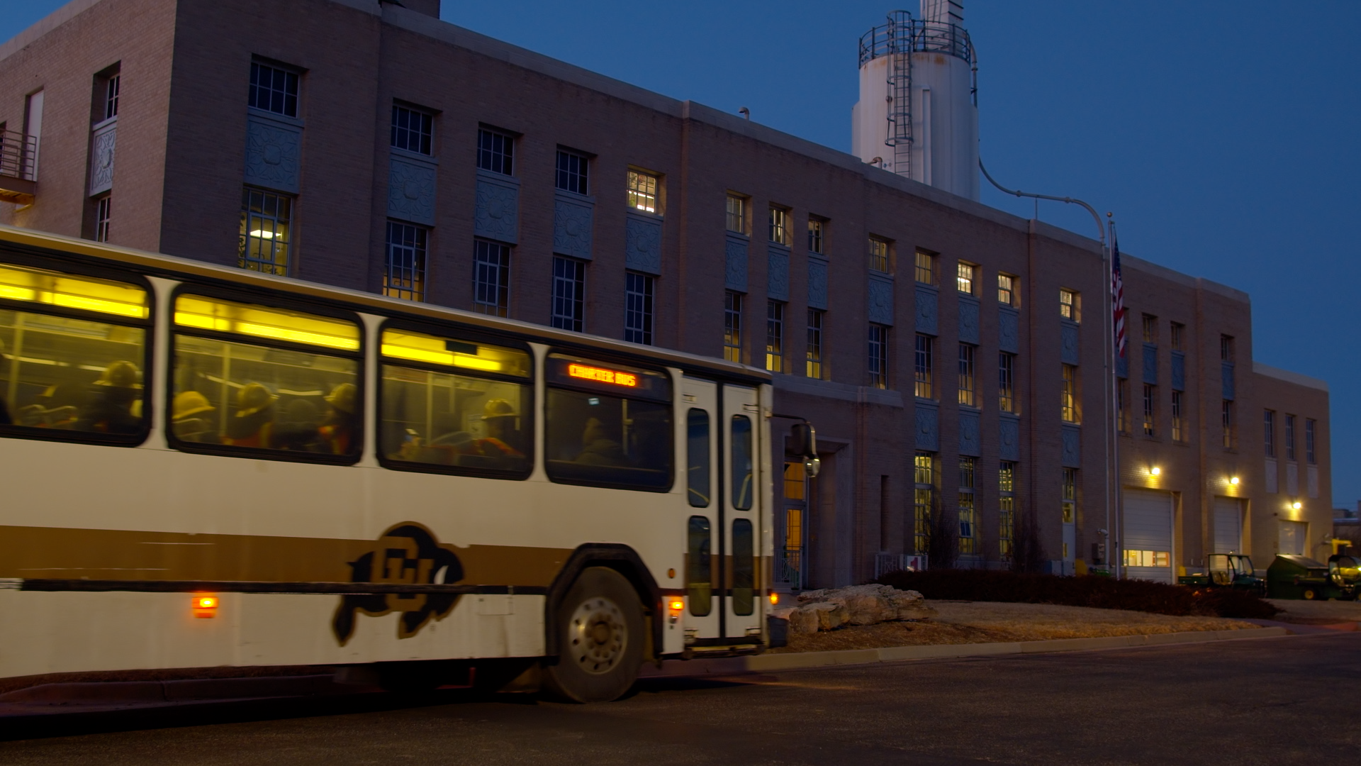 A bus with the logo of the CU rams on the side is in front of a large building at dusk, with the lights.