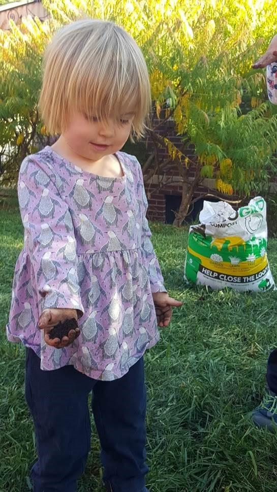 Serena Tejral helps her family spread EcoGro on the lawn. The compost originates with compostable waste products from Denver. Photo credit: Denver Water.