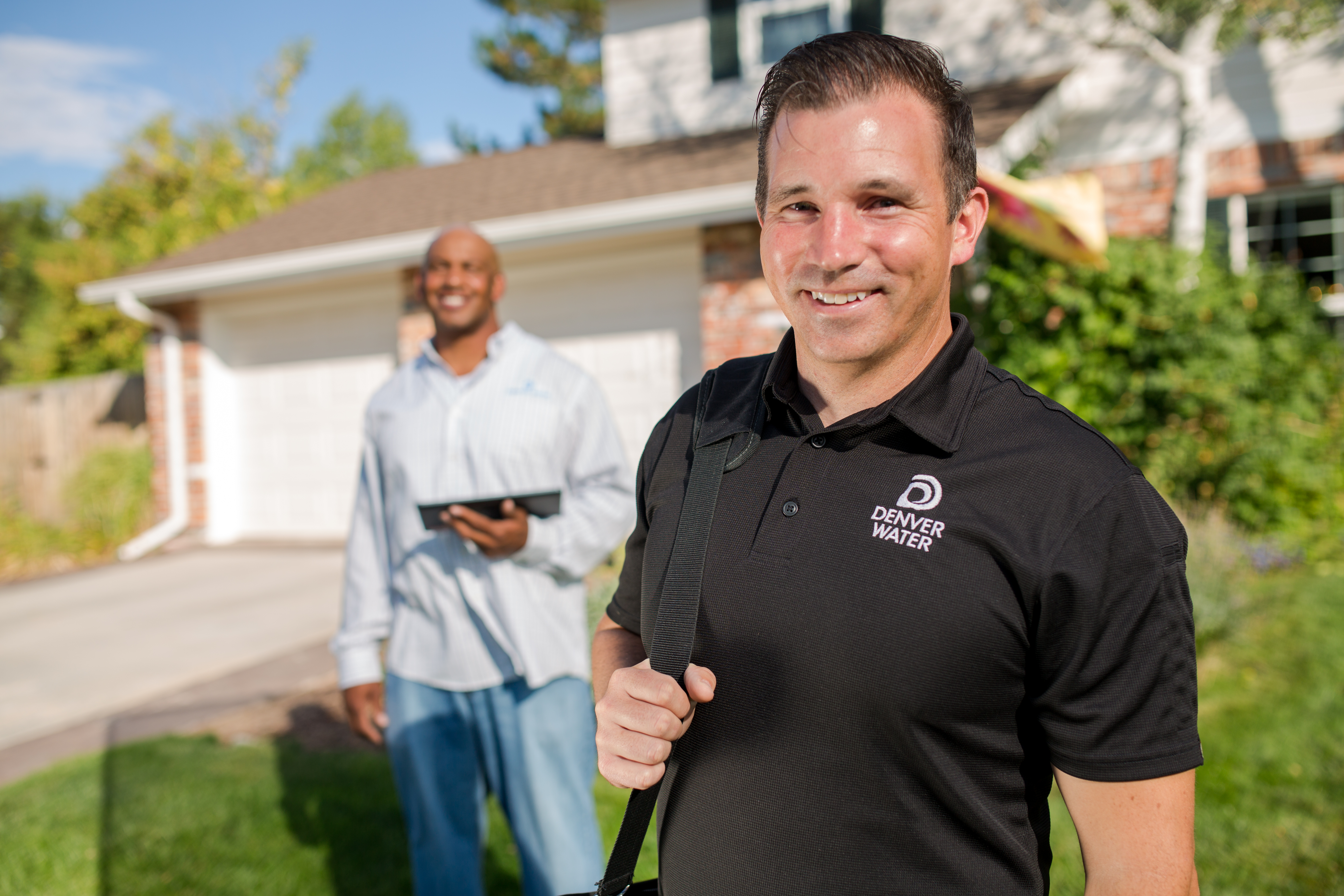 Two men with Denver Water shirts stand in front of a home, smiling for the camera.