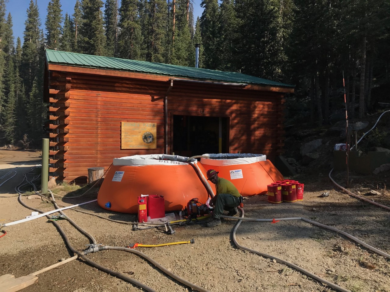 A U.S. Forest Service firefighter sets up a water storage tank to run sprinklers around a building at Denver Water's Jone Pass facility. Photo credit: U.S. Forest Service.