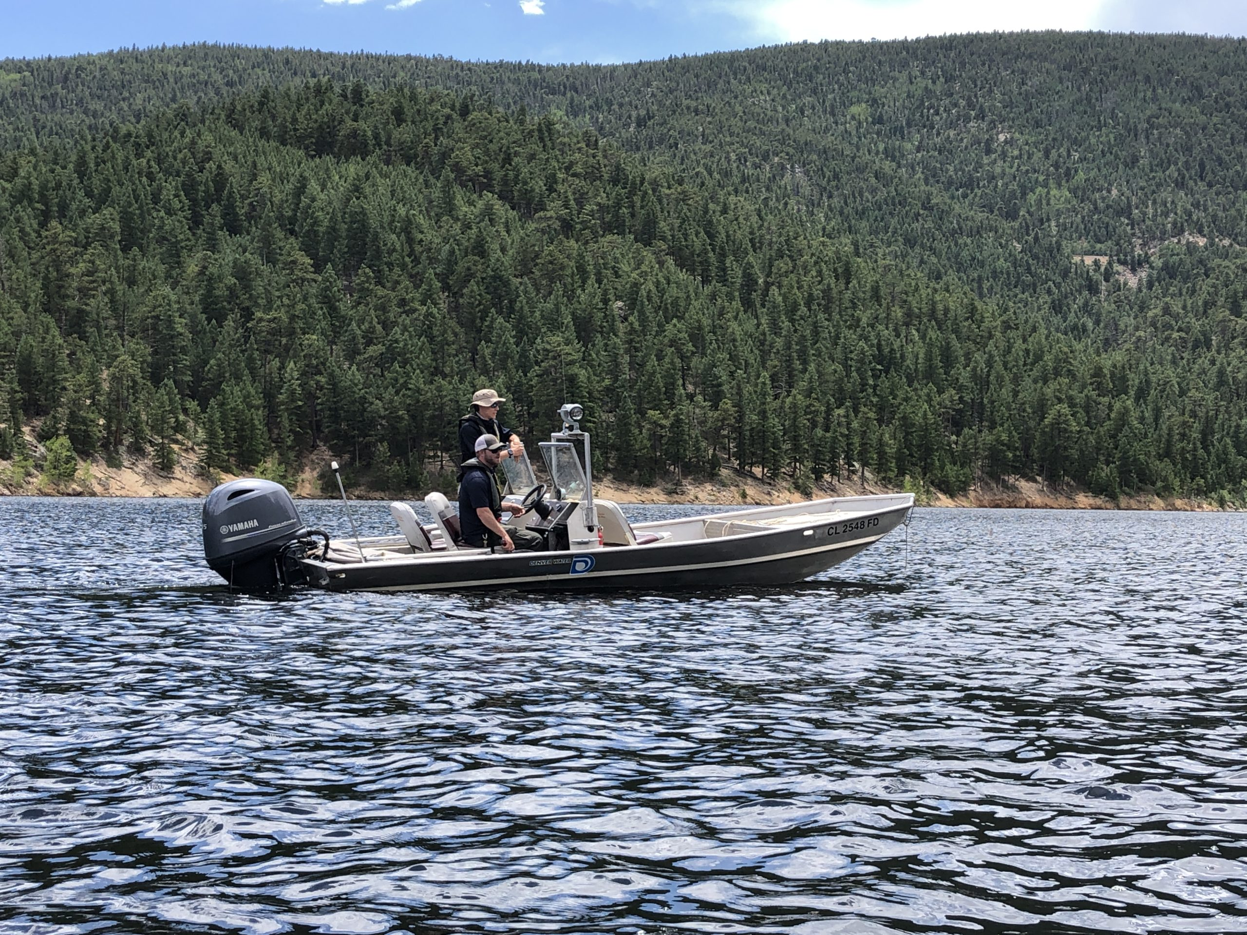 Two men on a small motor boat on a reservoir in the mountains.