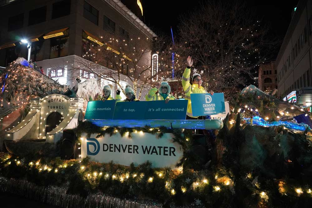 "Volunteers hold signs that say ""From mountain to tap, it's all connected"" and wave from the top of a float."
