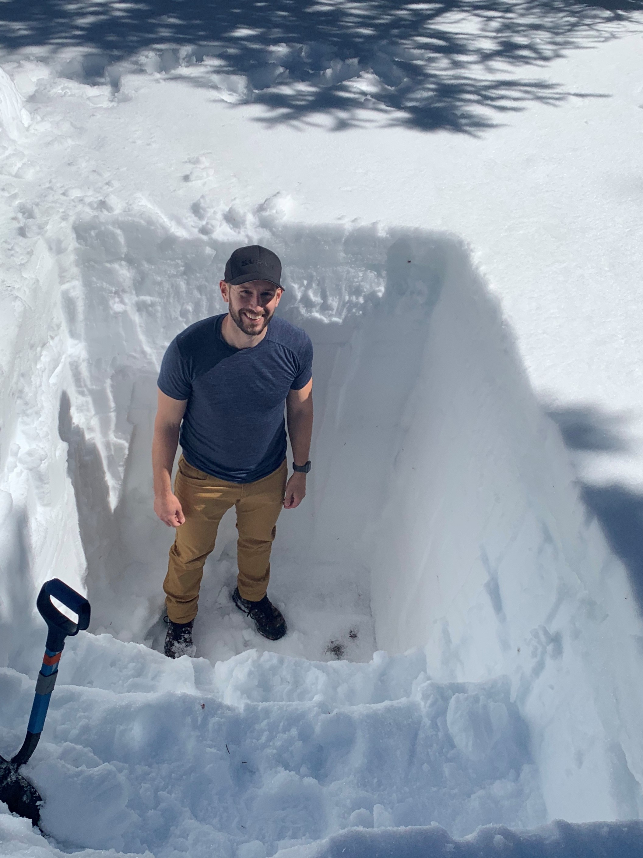 A man stands at the bottom of a pit carved out of snow, smiling up at the camera. The pit is about as deep as he is tall.