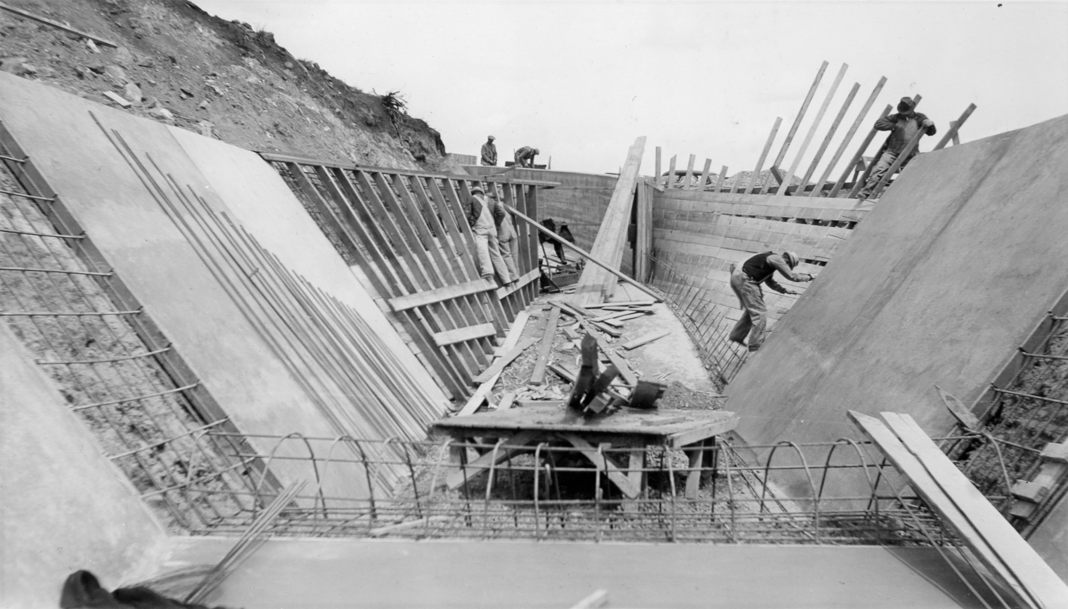 A black and white photo shows construction workers and scafolding building a canal.