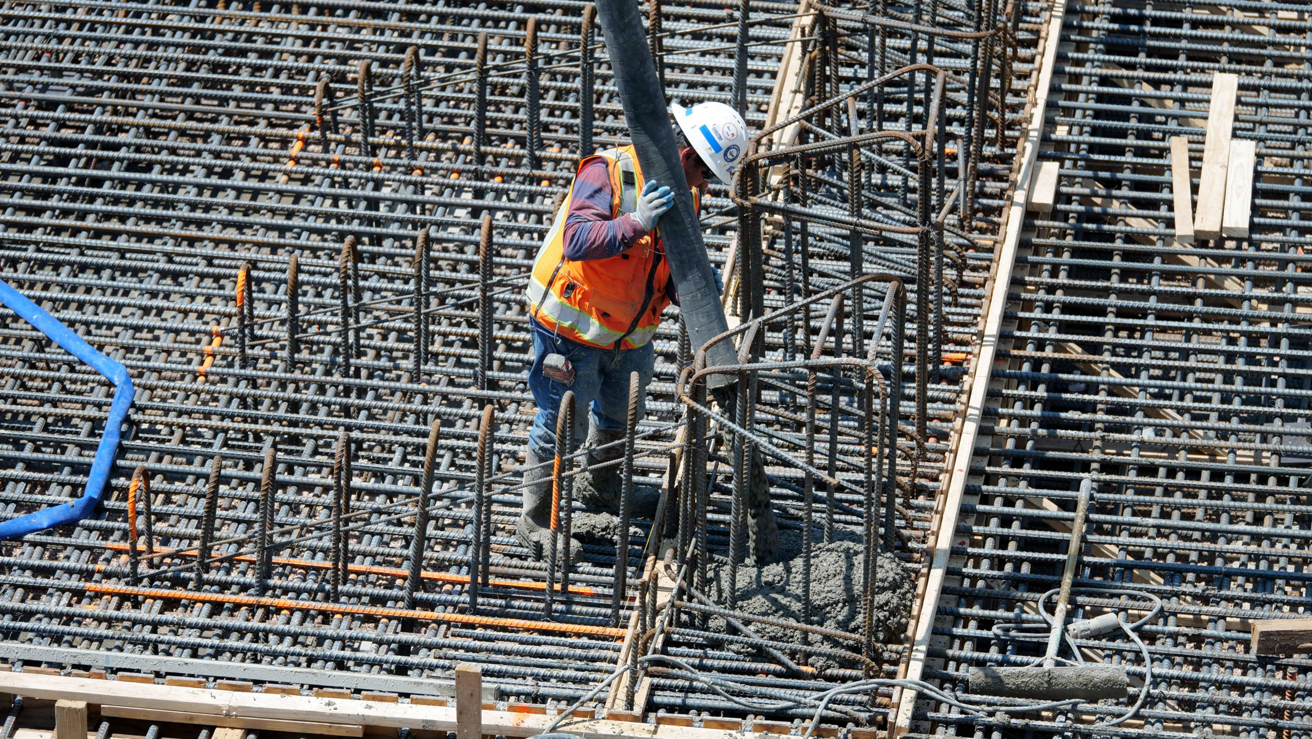A man surrounded by concrete reinforcing bar, or rebar, pours concrete from a tube.