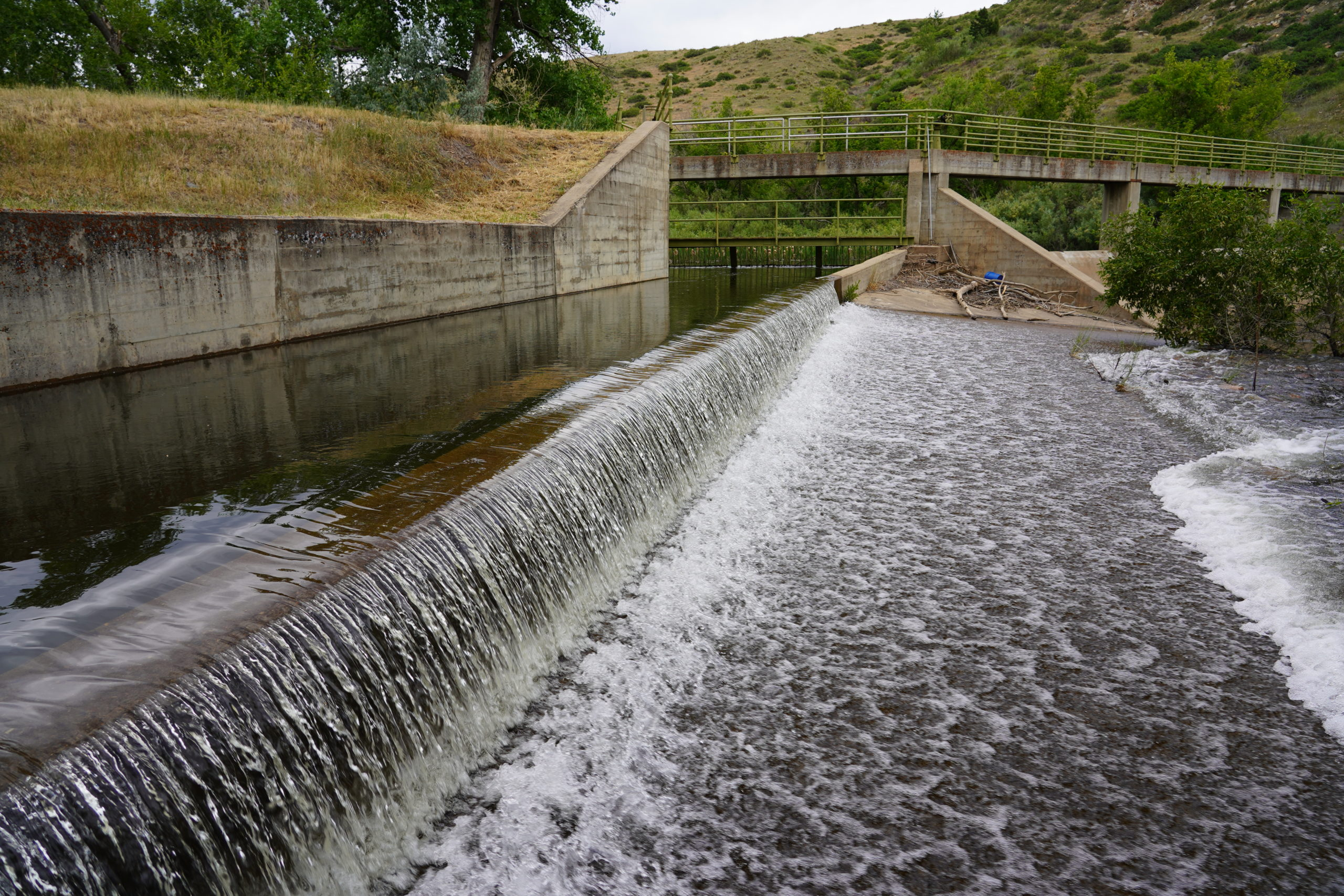 Water flows over a concrete dam.