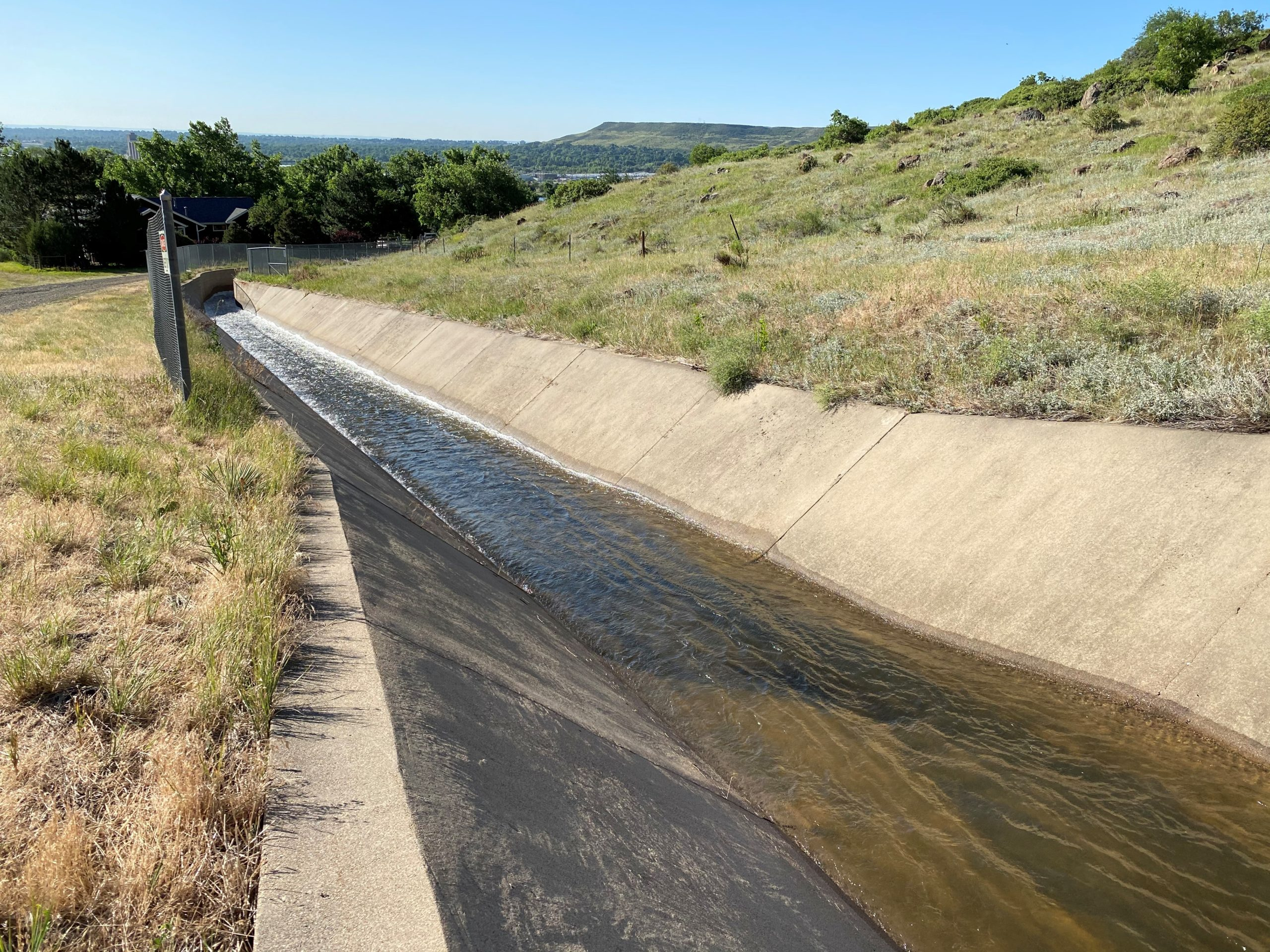 Water flows down a concrete canal.