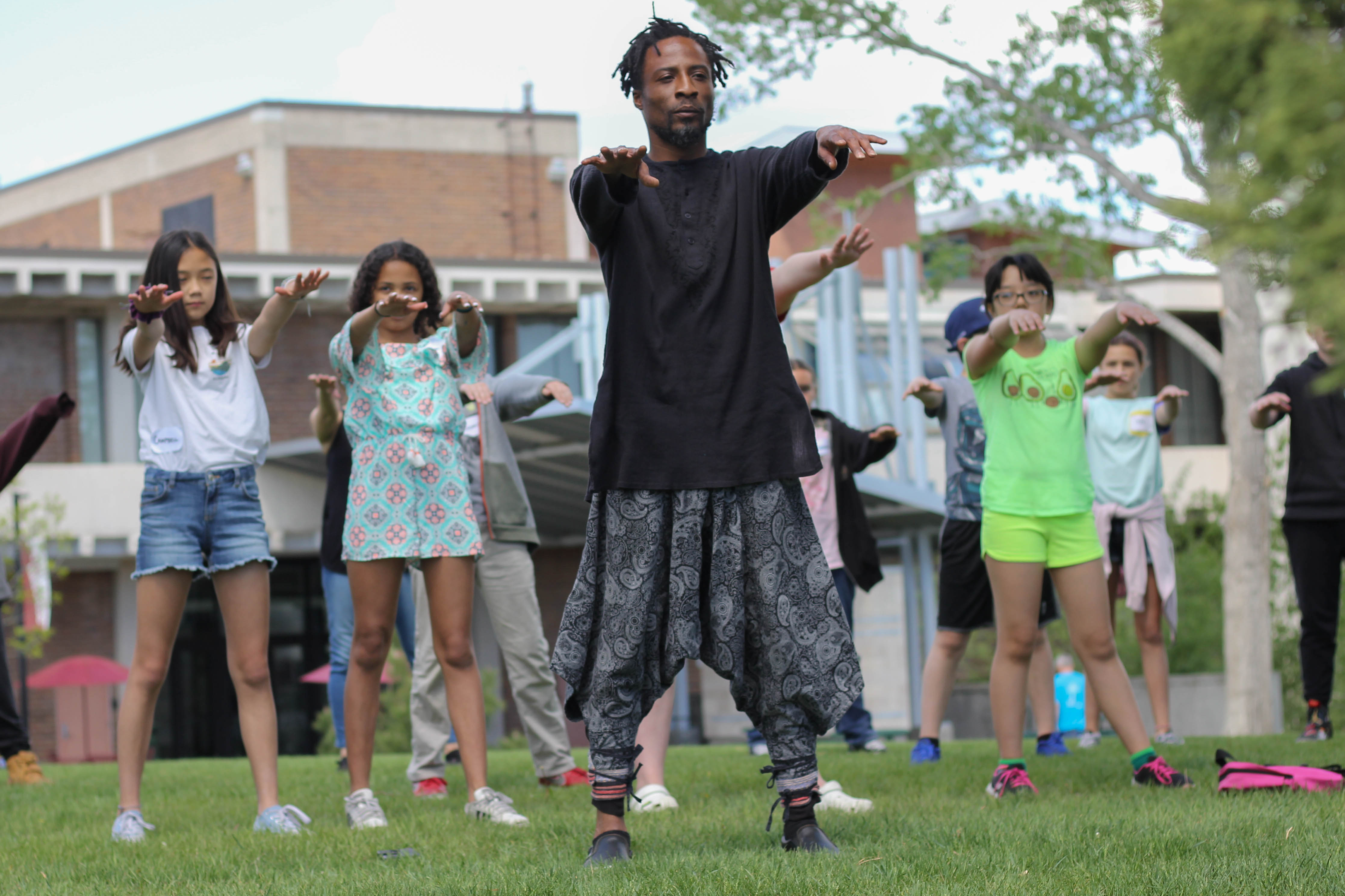 A man in a black top and grey pants holds a tai chi pose, with his feet planted and arms held out in front of him. In the background, several children mimic his movement.