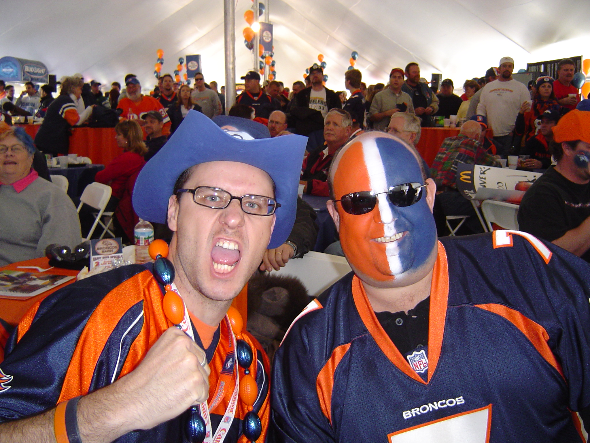 Two men in Denver Broncos gear, one with orange and blue face paint, cheer for the camera.