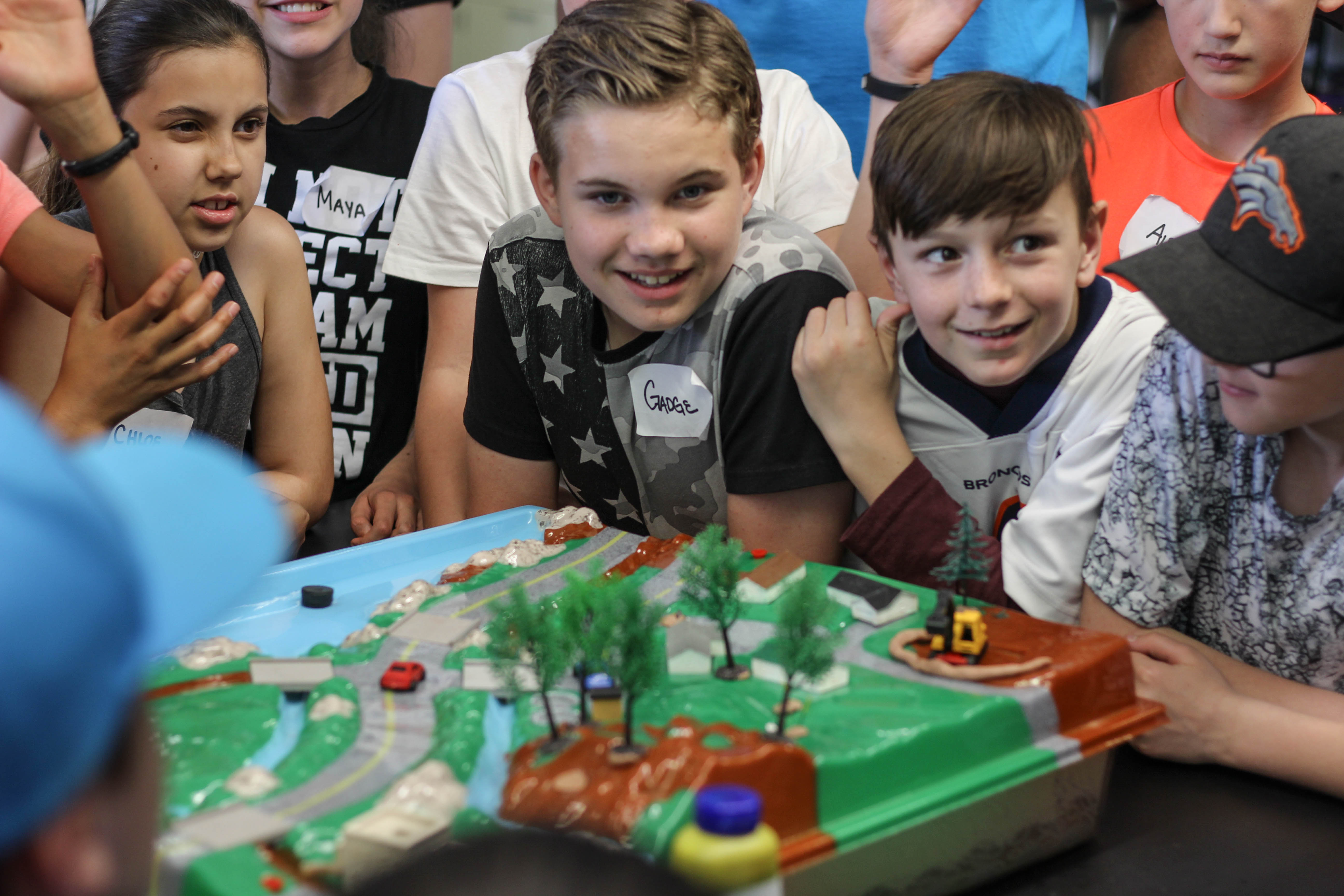A group of children surround a plastic cityscape, with tiny trees, roads and cars.