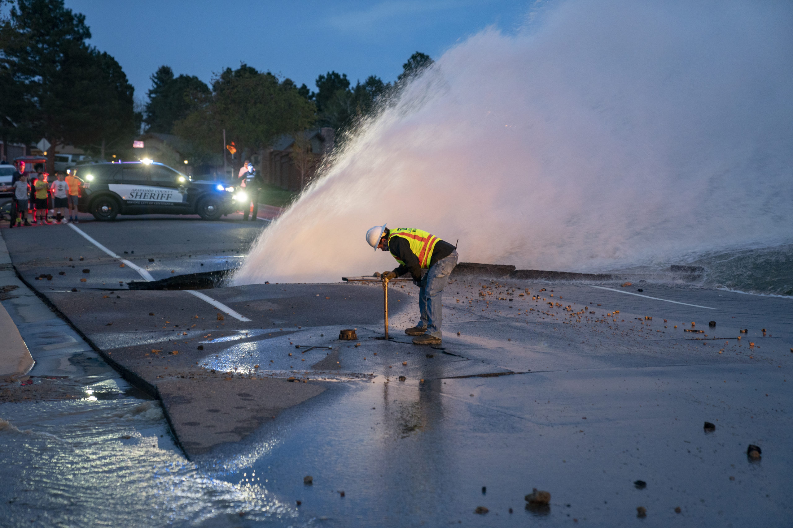 A man in a Denver Water vest is dwarfed by a geyser of water shooting out of a rupture in the street.